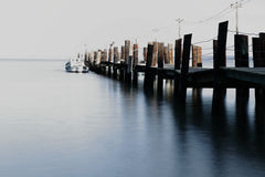 Sea, boat and wharf. Long exposure. Stock Photos