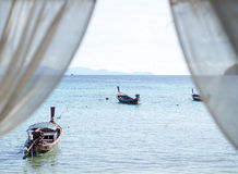 Sea, boats from hotel room window, white curtain. Sea and boats with skyline view from hotel room window and white curtain; selective focus on sea background Stock Image