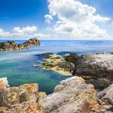 Sea boulders under cloudy sky. Sea wave wash colorful sea boulders under cloudy sky royalty free stock photos