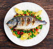 Sea bream baked with herbs and lemon, vegetable mix. Stock Photo
