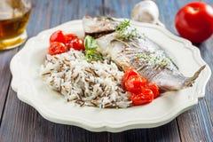 Sea bream/Dorado baked with tomato confit and rice Stock Photos