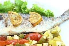 Sea Bream fish with vegetables. On a white plate Stock Photo