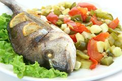 Sea Bream fish with vegetables. On a white plate Royalty Free Stock Images