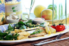 Sea Bream & salad. Grilled sea bream topped with parsely, tomatoes, baby spinach salad with balsamic vinaigrette and pine nuts. Wine glass repositioned, altered Royalty Free Stock Photo