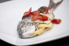 Sea bream with tomatoes and lemon Royalty Free Stock Photography