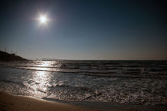 Sea with bright sun on dark blue sky Royalty Free Stock Photography
