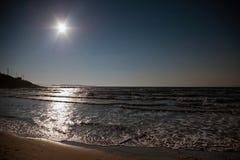 Sea with bright sun on dark blue sky royalty free stock photography