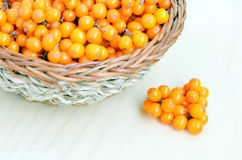 Sea-buckthorn berries in basket on a wood background Royalty Free Stock Images
