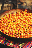 Sea-buckthorn berries in rustic brass bowl, farm style Stock Images
