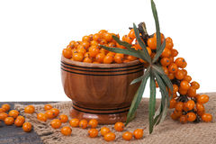 Sea-buckthorn berries in a wooden bowl on table   white background. Sea-buckthorn berries in a wooden bowl on a table  on white background Royalty Free Stock Photography