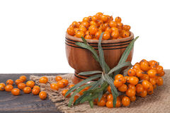 Sea-buckthorn berries in a wooden bowl on table   white background. Sea-buckthorn berries in a wooden bowl on a table  on white background Stock Photo
