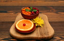 Sea buckthorn and cranberry  with leaf of mint near the slice of orange Royalty Free Stock Photography