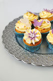 Sea buckthorn cupcakes. Silver platter of flowery yellow-blue cupcakes on white background Royalty Free Stock Photos