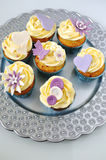 Sea buckthorn cupcakes on silver platter. Silver platter of flowery yellow-blue cupcakes on white background with butterflies and buttons Stock Images