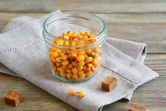Sea-buckthorn in a glass jar on linen napkin Royalty Free Stock Photos