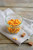 Sea-buckthorn in a glass jar on napkin Stock Photo