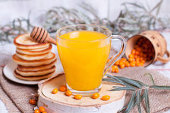 Sea buckthorn juice and berries. On a wooden board Royalty Free Stock Photography