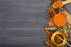 Sea buckthorn juice or tea with honey on a black wooden background with copy space for your text. Top view Stock Photo