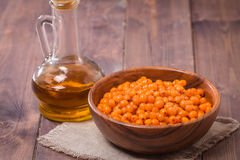 Sea-buckthorn oil and berries Royalty Free Stock Photo