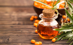 Sea buckthorn oil at right side of wooden background Royalty Free Stock Image