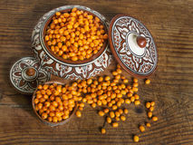 Sea buckthorn orange berry and African handmade ceramics Royalty Free Stock Image