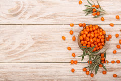 Sea buckthorn. Ripe fresh berries in bowl on white wooden background with copy space for your text. Top view.  royalty free stock photo