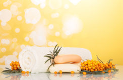 Sea buckthorn soap and white towel on abstract yellow. Royalty Free Stock Photography