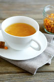 Sea-buckthorn tea in a cup on the linean napkin Royalty Free Stock Photography