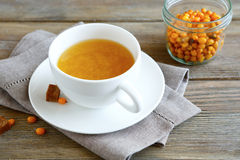 Sea-buckthorn tea in a cup on wooden boards Royalty Free Stock Image