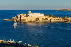 Sea, building on rock and ship, St. George ´s bay, Malta. Sea background with ship and building on rock in sunny evening, St. George ´s bay, St. Julian ´s Stock Image