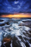 Sea Bungan Dark Vert. Dark dawn time at Bungan beach of Pacific coast in Sydney, Australia. Strong waves roll on eroded boulders under orange rising sun stock images
