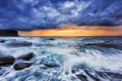 Sea Bungan Front Cloud Rise. Stormy weather from open Pacific Ocean at Bungan beach of Sydney northern beaches with orange rising sun under thick clouds Royalty Free Stock Photo