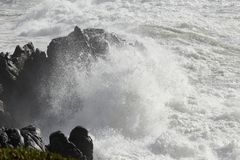 Sea cape being hit by wave Stock Photography