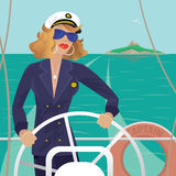 Sea captain female on the deck with ships steering wheel. Serious female sea captain standing on the deck of the ship and rotates ship steering wheel. Sunny Stock Photography