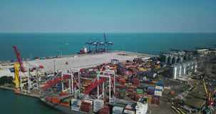 Sea cargo port with big warehouse. Odessa, Ukraine - 24 July 2017: Sea port with a large warehouse with many multicolored containers. There are big cranes stock video