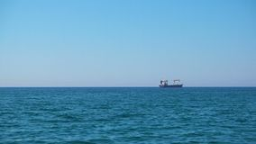 Sea and cargo ship. Calm sea with clear blue sky and cargo ship on the horizon stock footage
