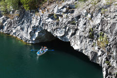 Sea cave in the marble. Republic of Karelia. Tourists in a boat floating in the cave. Wild raw marble.  Ancient Marble quarry, marble rocks in the wild Stock Photography