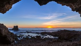 Sea cave at sunset with light clouds and pink and orange hues over the Pacific Ocean in Orange County, California.