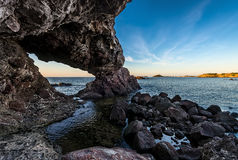 Sea Caves, Rocks and Sea View in Sardegna, Italy. Panoramic view to the sea, rocky coast, water cave and Nora tower near Pula in Sardegna, Italy. Wide angle stock image