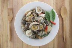 Sea clams or RIDGED VENUS CLAM of Stir sauce in white dish. Sea clams or RIDGED VENUS CLAM of Stir sauce in white dish on wood background Royalty Free Stock Photos