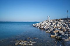 Sea and clear sky landscape with hut on the white rock streak Long exposure photograph Stock Images