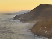 Sea Cliff bridge yellow distant. Australia Grand Pacific drive sea cliff bridge at the coast above the pacific ocean at sunset distant under yellow setting sun Stock Photography
