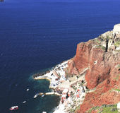 The sea cliff and old port in Oia,Santorini. An aerial view of old port at the foot of cliff royalty free stock images