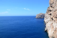 Sea cliffs and island, Sardinia Stock Photo