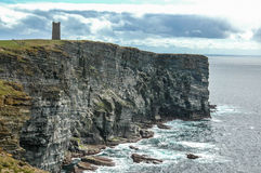 Sea cliffs with medieval tower in Orkeny Scotland. View of sea cliffs rising from the ocean with a medieval tower in Orkney, Scotland, UK Stock Images