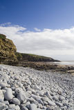 Sea Cliffs and Pebbles. Gray rounded rocks on storm beach at Southerndown, South Wales, UK royalty free stock photography
