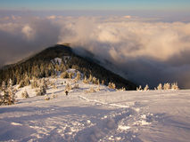 Sea of clouds. Snow path descending towards a sunny ridge with a sea of clods covering the lower part of the mountain Royalty Free Stock Images