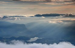Sea of clouds, mist and sun rays at sunset, Lake Bled, Slovenia. Sea of clouds and autumn mist illuminated by setting sun above Lake Bled, Bohinj mountain range Stock Image