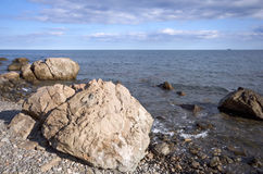 Sea coast with boulders and stones against the sky. Black sea coast with boulders, stones, pebbles against the small trip at the horizont and the blue sky with Stock Photos