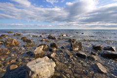 Sea coast with boulders, stones and clear water. Black sea coast with boulders, stones, pebbles and clear transparent water against the blue sky with clouds Stock Photography